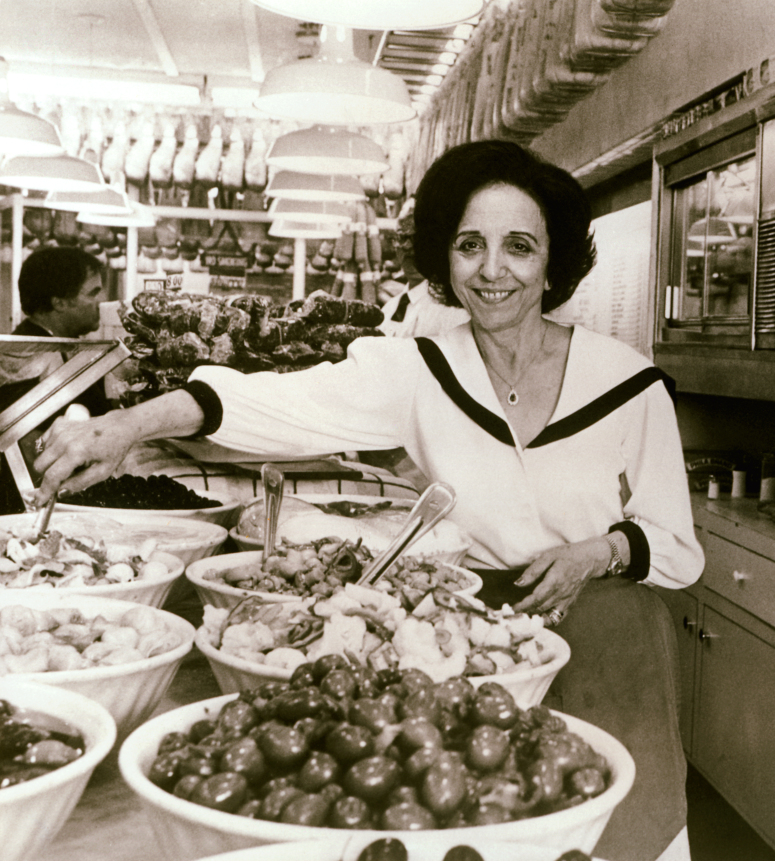 'Mama' Carmela Sbarro, a tall Italian woman with short, dark hair, stands in line with eight Italian dishes prepared at the original Sbarro